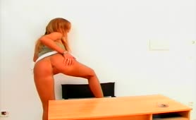 Blonde secretary pooping on a wooden desk