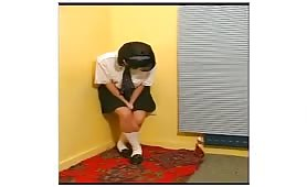 Young school girl peeing on bedroom floor